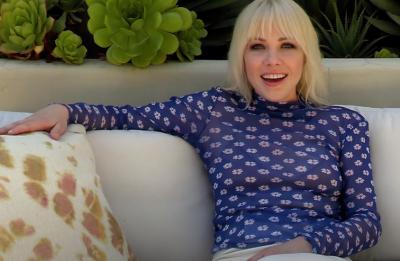 Carly sentada em um sofá (Reprodução)
