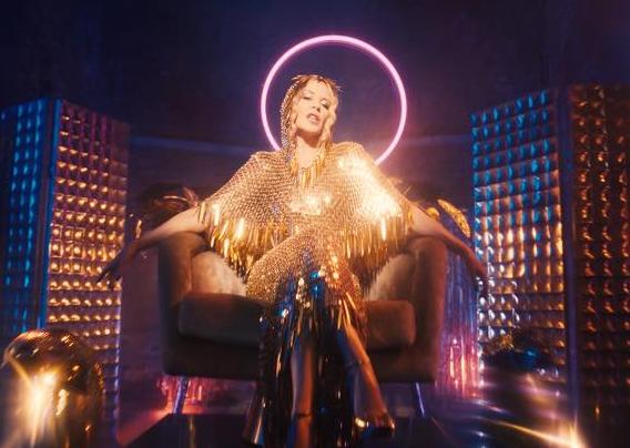 Kylie Minogue sentada em uma poltrona (Foto: Reprodução)