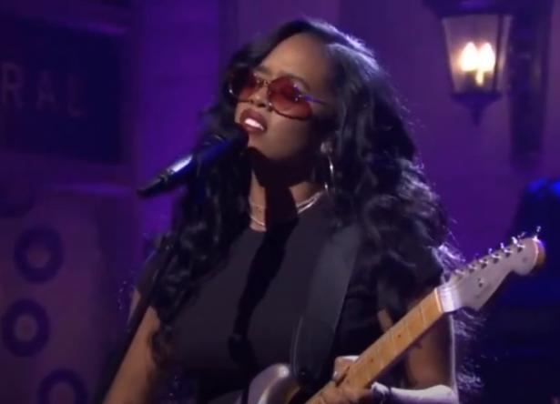 H.E.R tocando guitarra e cantando no microfone (Reprodução)