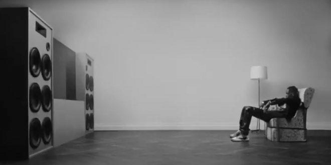 Travis Scott sentado em um sofá (Reprodução)