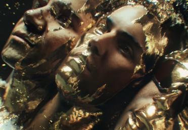 O vídeo traz cenas dos artistas sendo revestidos em ouro (Reprodução / YouTube)